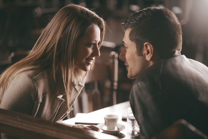 Man and woman flirting in a coffee shop. Leaning in to kiss.