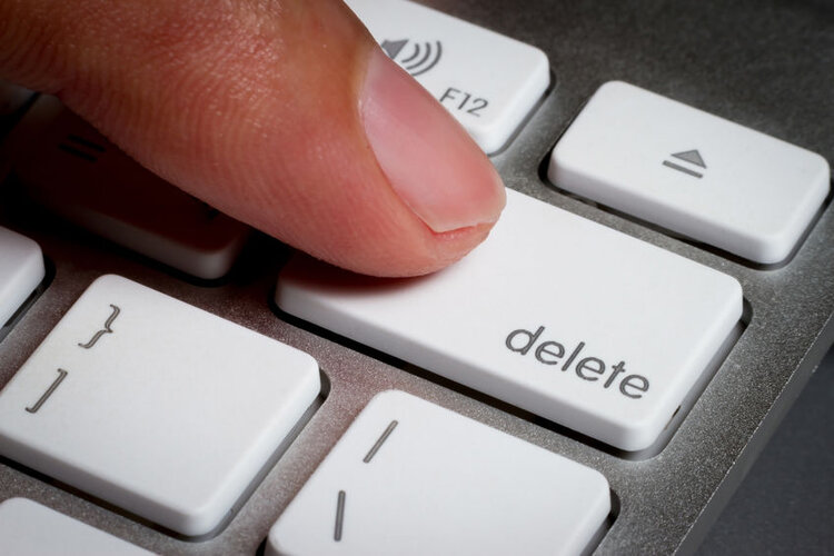 Pressing delete button on computer keyboard.