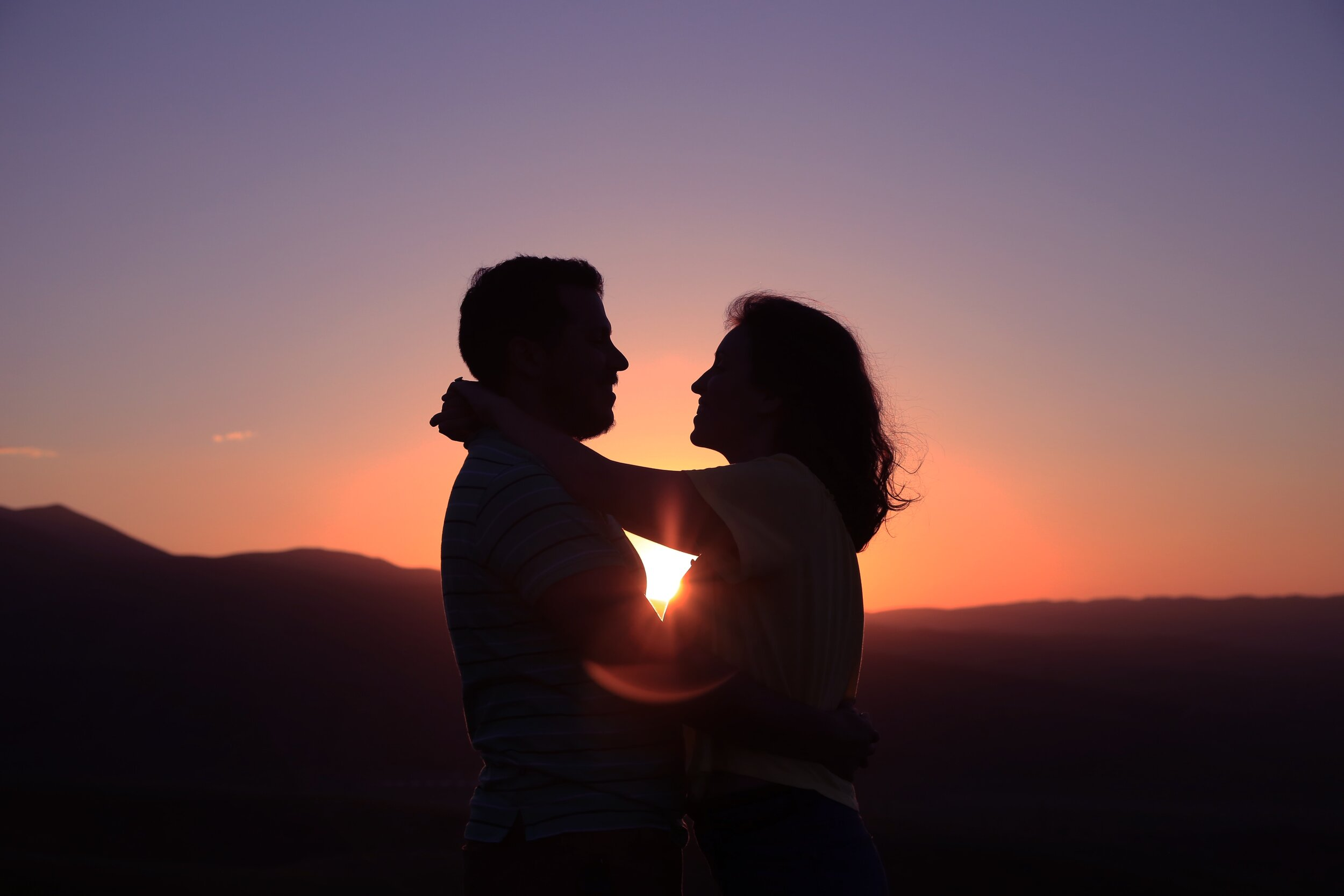 Love. Couple embracing in the sunset.
