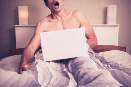 Man masturbating in bed with laptop.