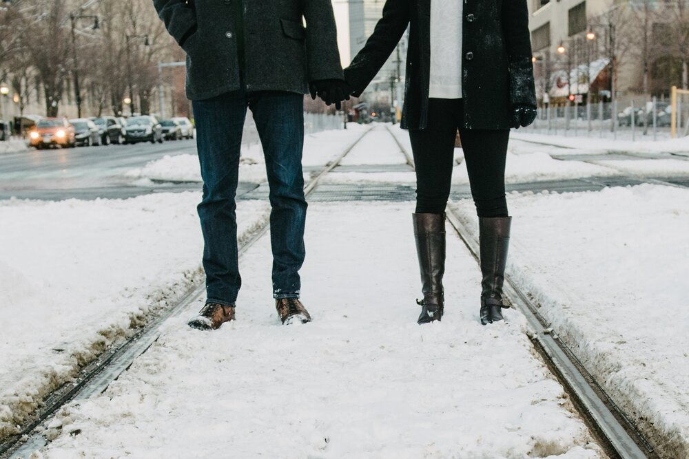Couple holding hands in winter. Snow on the streets.