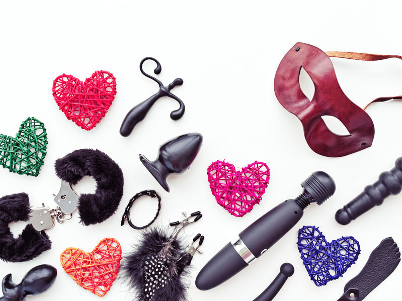 Collection of sex toys, including masks, vibrators, and butt plugs.