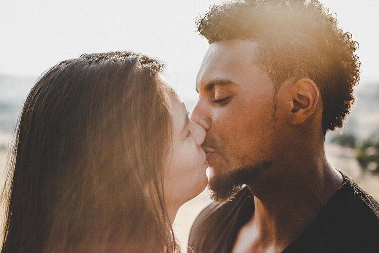 Межрасовая пара страстно целуется.