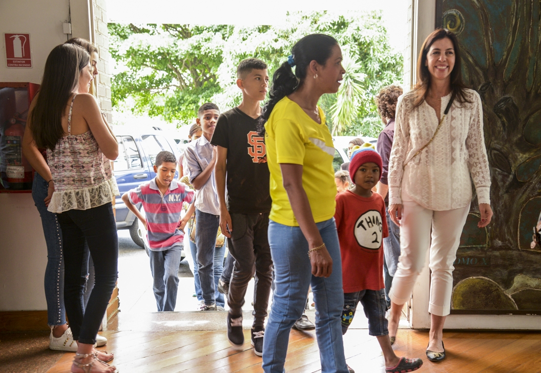 Elizabeth Schummer pictured here with students from her recent photography project in Caracas.