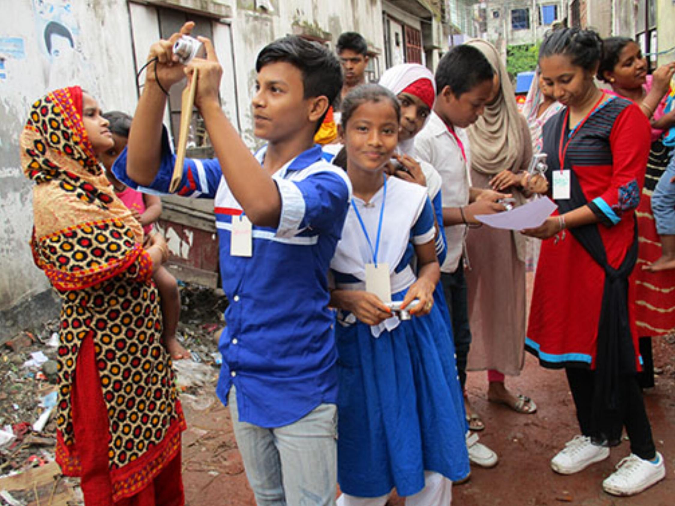 100cameras Snapshot Dhaka students practice camera skills during photo drills, Nuru Chala neighborhood.