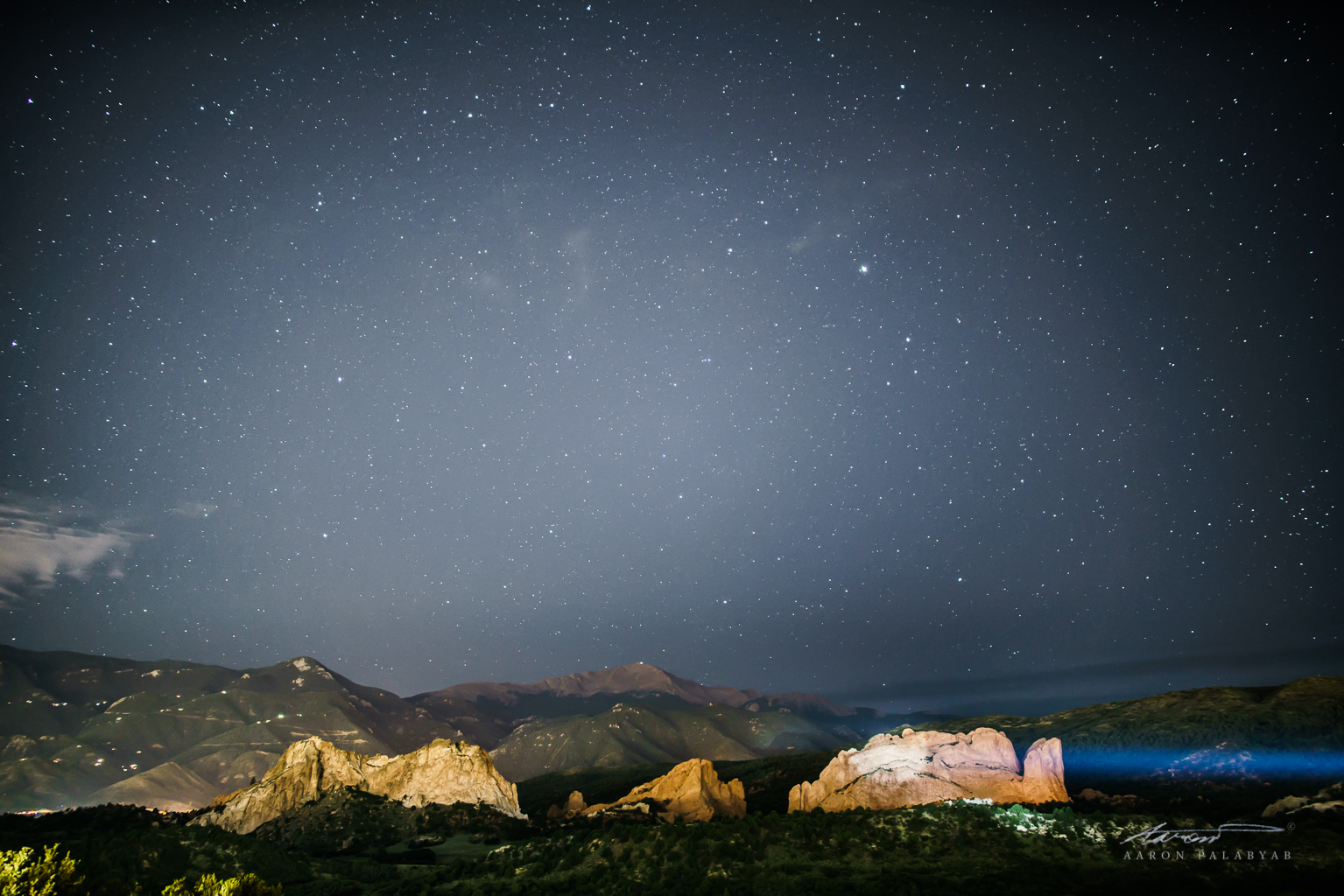 Stars over Pike's Peak and the Garden of the Gods, with a spotlight falling on (I think) the Kissing Camels rock formation