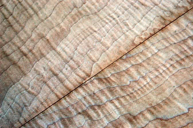 Adjust the veneer until you have a good pattern to the grain, and mark where the trim must be.