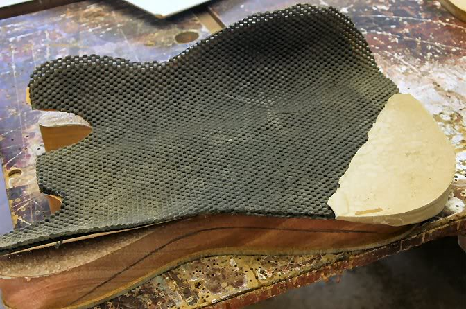 """My choice, apply a couple of pads I cut from """"Non Slip"""" work table pads. You will notice the """"block"""" I have made to take up the void left by the curve of the contour. To make it, I took a body, put down a sheet of plastic and filled it in with Auto Body Putty, let it harden and shaped it so the top would be flat with the pads. The pads are about ½"""" thick so they take up any inaccuracy as the filler block is used with other bodies."""