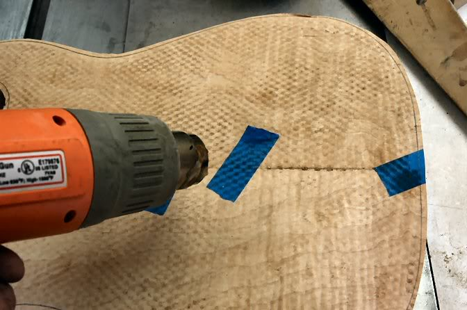 It's pretty ugly at this point, but take a heat gun, hair dryer, or whatever to soften the well stuck tape and remove it. The heat allows the adhesive to release without pulling fibers or worse, chunks out of the veneer.