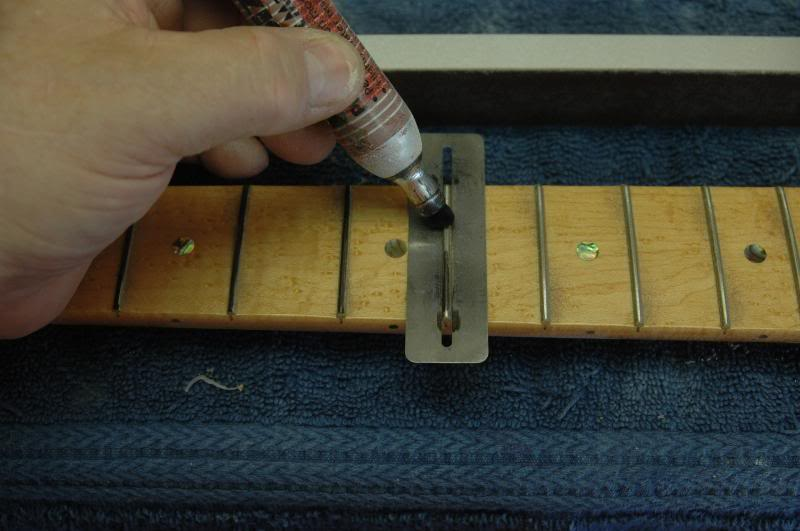 "Now, I recommend taking a marker, and coloring each fret. This makes seeing what you are doing much easier, and you can fine tune your truss rod leveling. Place your leveling tool on the fingerboard and give it a shove, remove and check the marked frets. If the end frets have been scraped and the middle ones not, then tighten the truss rod a touch and repeat. Continue until the frets toward the center of the fingerboard are being ""hit"" too. Now re-coat all the frets with the marker, and recheck. If the majority of the frets show exposed metal from the fret leveling tool, you are ready to rock."