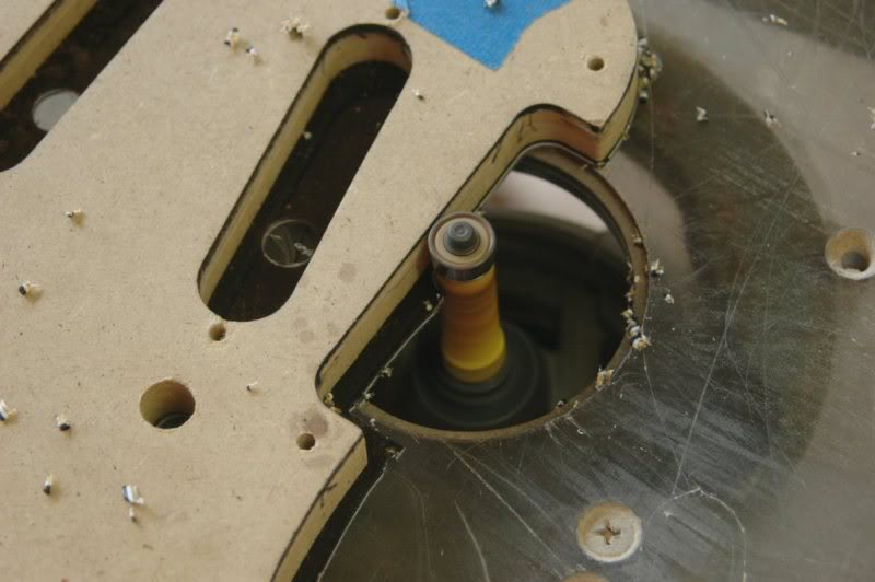 Then over to the router table to circumnavigate the periphery of the pick guard with a straight edge bit.