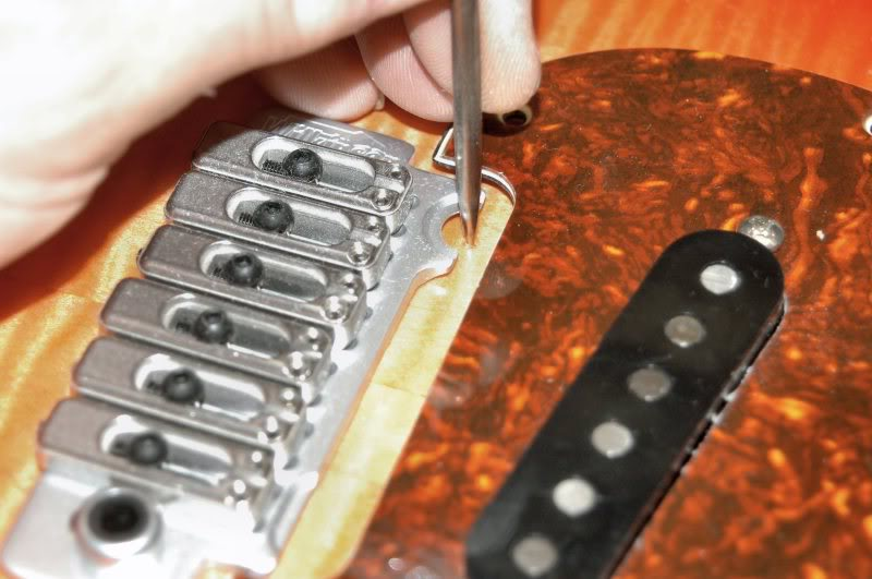 "Now I insert the neck, place the pickguard in position, then place the tremolo in the correct position. Measuring from the 12 fret, locate the first bridge 12 ¾"", and that'll be the location of the tremolo. Since the neck and pickguard are in place, I give it a good look to be certain everything looks correctly positioned. I use a 4 foot ruler to indicate the position of the strings and make any adjustments as necessary. Then mark the location of the posts for the Tremolo, here, the Wilkinson VS100."