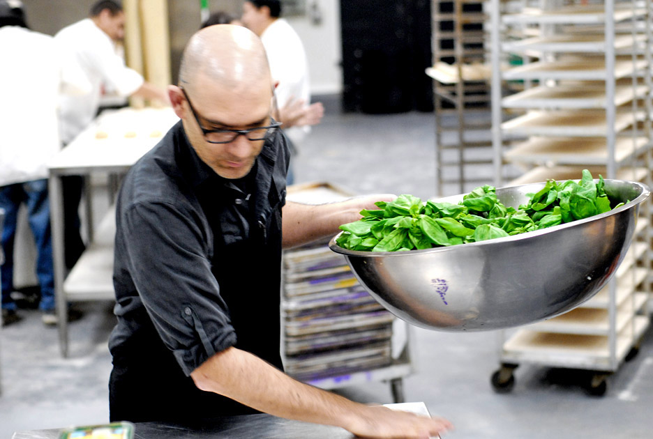 Jorge preps pounds of fresh basil to be chopped and added to our sauces.