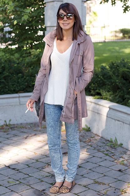 University of Toronto student enjoys a morning smoke. She is wearing a tan grey trench coat over a white top, faded blue jeans and leopard print flats.