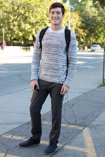 University of Toronto student wears a low scoop neck grey and white wool patterned sweater over a t-shirt, brown wool pants and blue suede oxfords