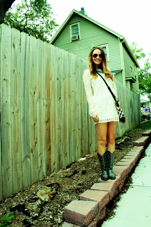 University of Kansas student wears a white long sleeved lace sleeve and trim dress with white trim black leather cowboy boots and ray ban aviators