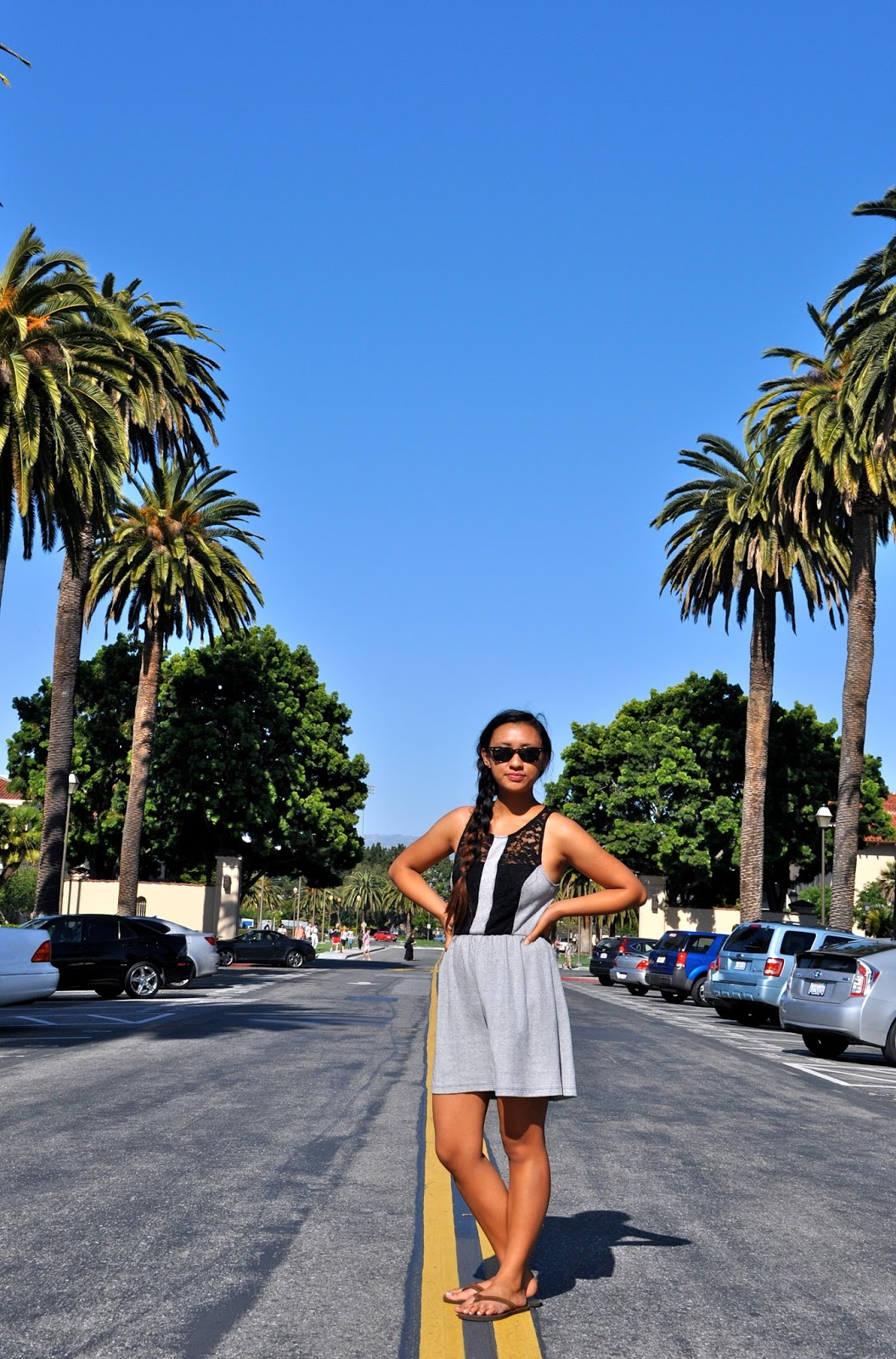 Anjelica, a Santa Clara University  student, sporting a grey herringbone dress with a black lace racerback and wearing her hair in a side ponytail