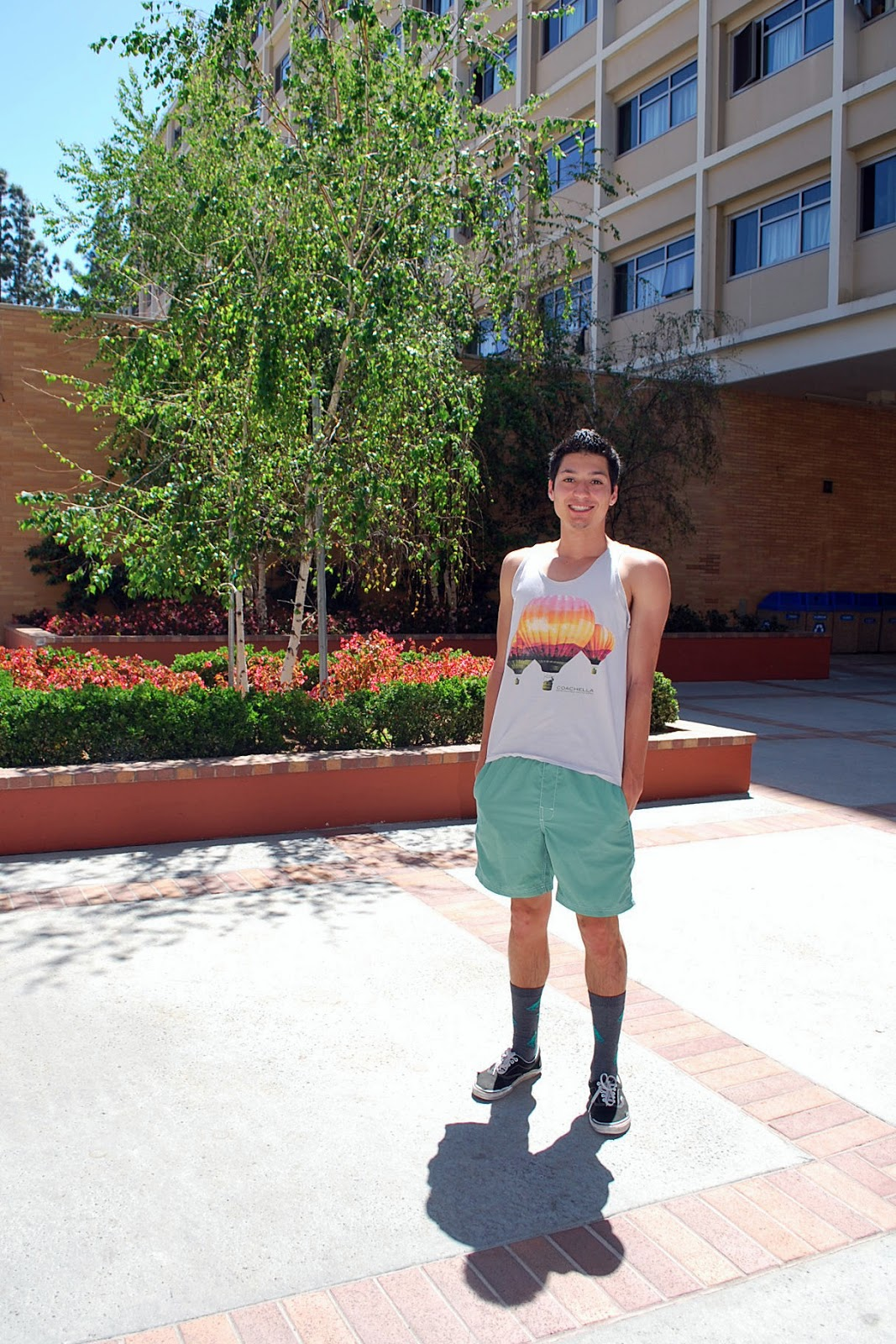 Max is a 1st Year student studying Civil Engineering. He is wearing a gray Coachella balloon print tank top over green shorts and green T-rex dinosaur socks and black vans