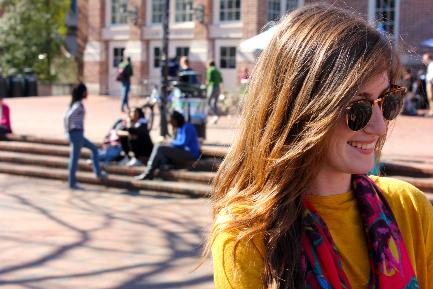 Sara C, a UNC Chapel Hill sophomore majoring in Journalism and Mass Communications wears a floral print pink/fuchsia scarf over a bright mustard yellow sweater, blue jeans and light brown suede chukka boots