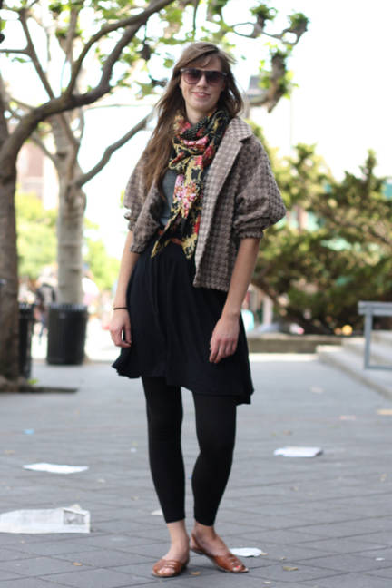 Marie wears a gray brown houndstooth cropped jacket over a gray shirt, black skirt and black leggings. Floral scarf and flats