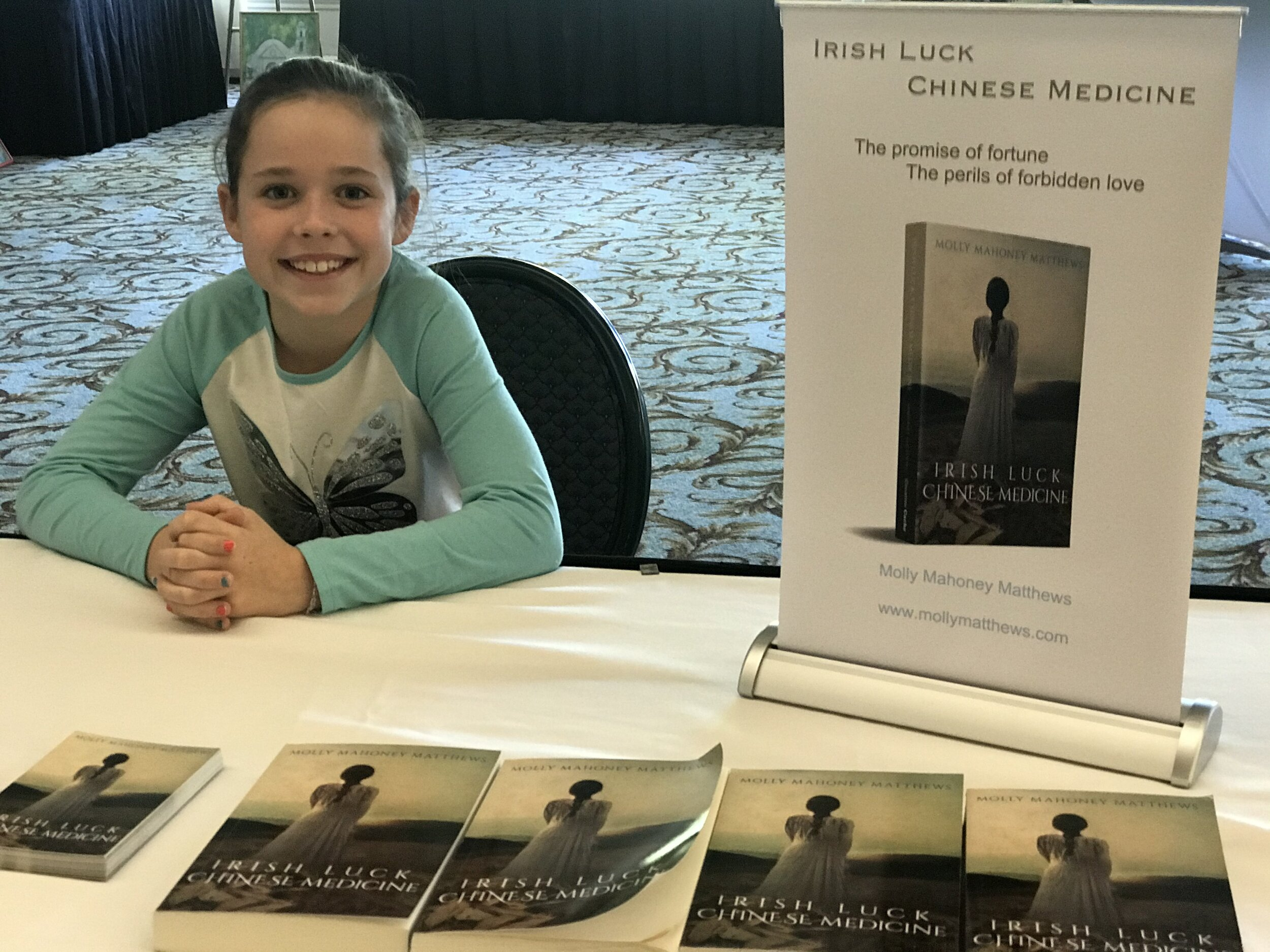 My granddaughter helping me set up for a reading at Kenwood's Art and Author Event.