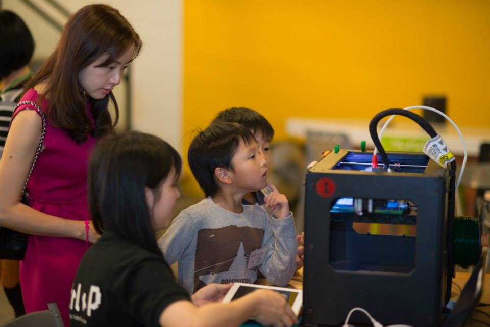 A staff guides a mother and children to the mechanics of a 3D Printer.