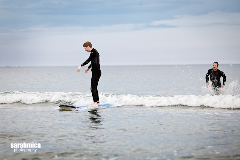 An elated Waypoint Adventurist stands up and rides a small wave while a volunteer runs after him