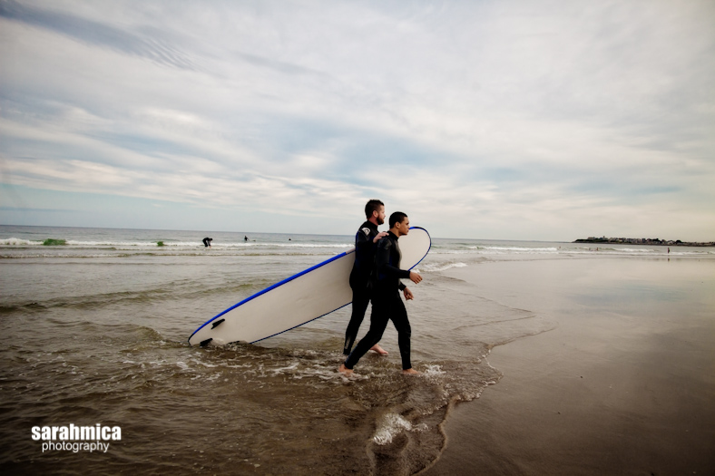 A Waypoint volunteer leads an adventurist out of the ocean and back to the shore