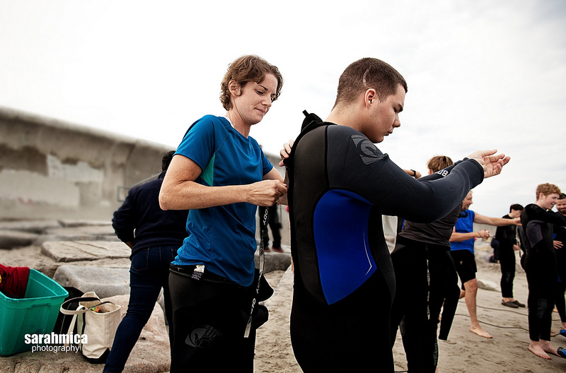 A volunteer helps an adventurist with his wetsuit.