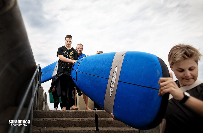 An adventurist (left) and a volunteer (right) carry a surf board down the stairs to the beach