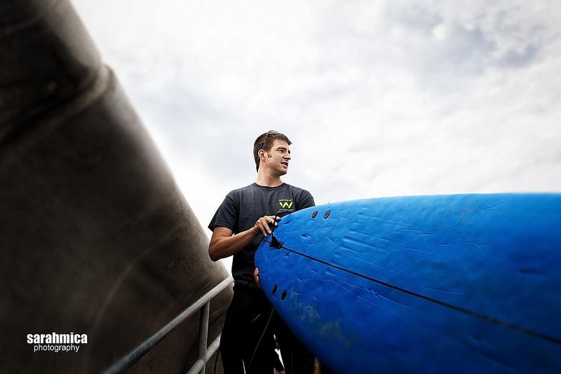 Dan carries a surf board through the beach entrance