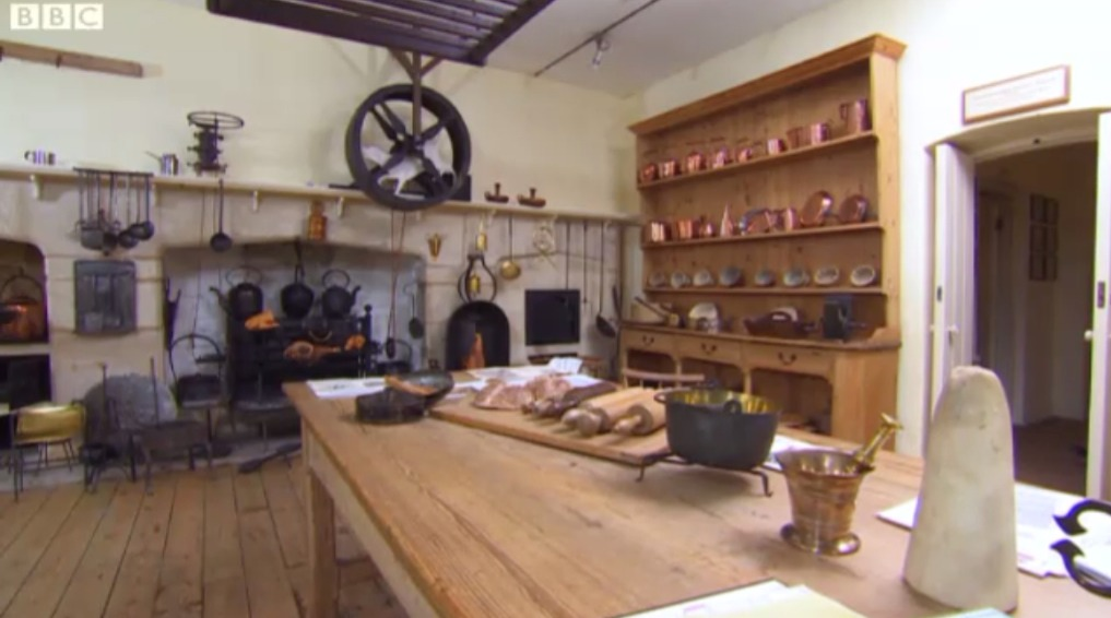 An 18th Century kitchen, courtesy of Austenonly. Notice the round wheel above the fireplace; this would have held a Turnspit Dog. Specifically bred for this task, the dog would spin the wheel and turn the spit for roasted meats.