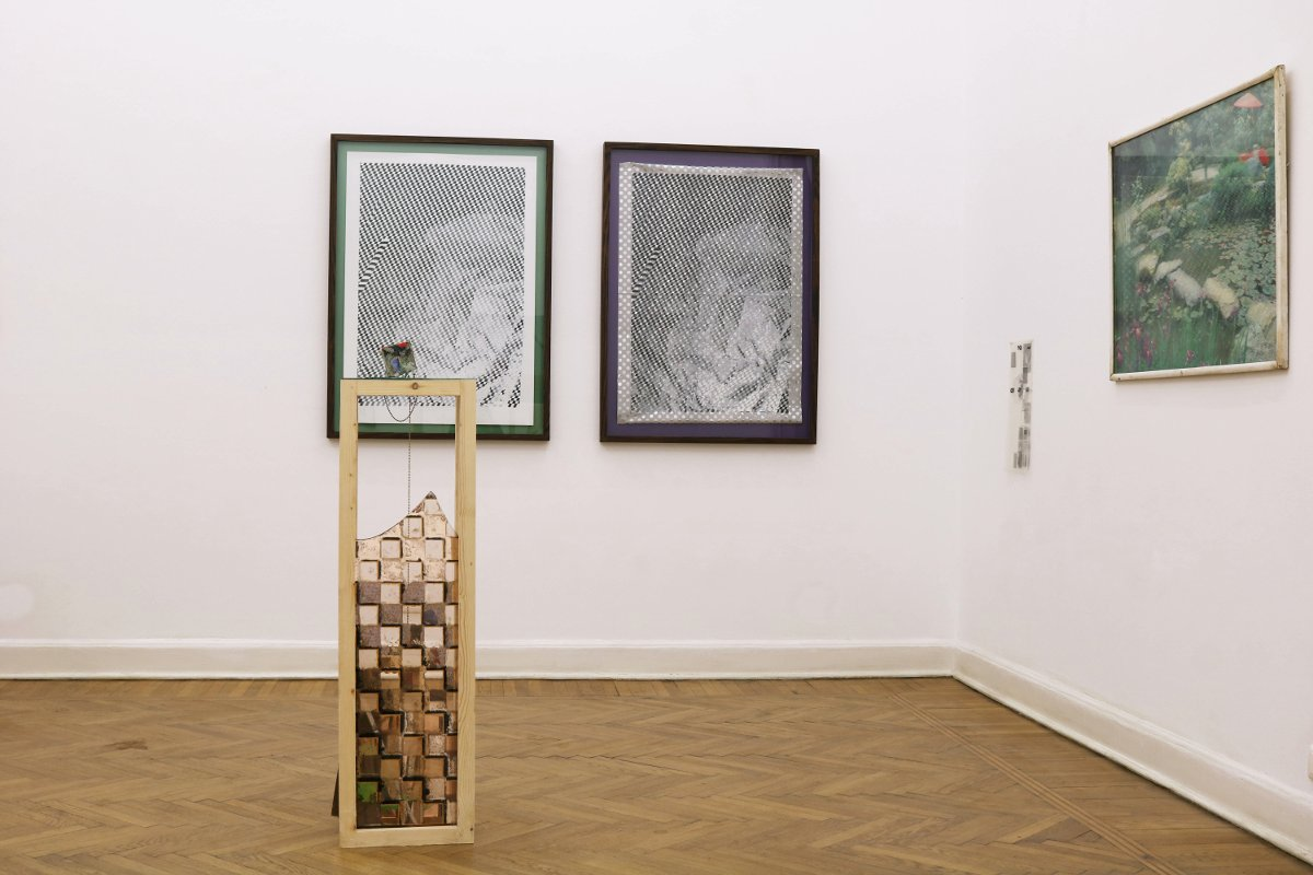 Installation view including framed picture/poster from ofce and transparencies found in the ofce. In the foreground cube sculpture (Paperweight #7) with wood pedestal. Pedestal with pieces of broken mirror and tinted mirror with silver backing scratched of to form checkerboard pattern. In the background: Untitled (part 1), 2016, Spray painted vinyl on polka dot wrapping paper, 60 cm x 90 cm;  Untitled (part 2), 2016, 60 cm x 90 cm, Spray painted vinyl on coated paper