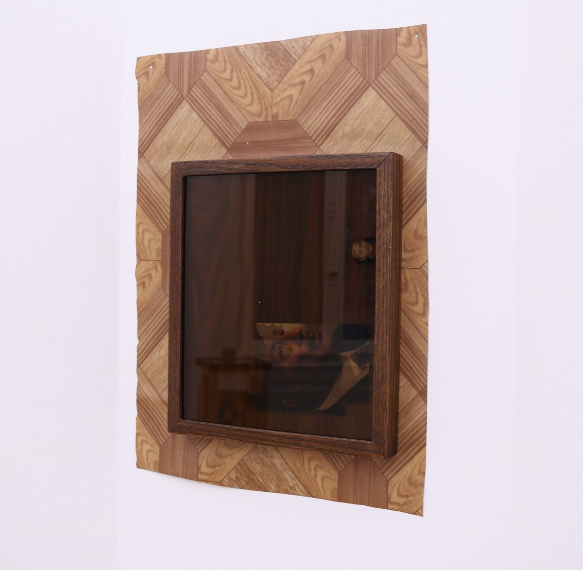 Untitled (clue), 2016, variable dimensions, PVC flooring on wall, wood frame (25 x 30 cm) with tinted glass and found photographs of uncle and Sadat, faux wood laminate backing.