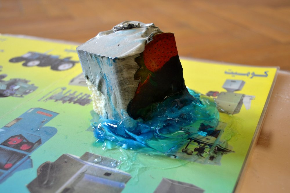"""Paperweight #1, detail, 2015/16, Installation view,materials: Concrete with cardboard, aluminium foil and expanded foam, blue """"Hair Code"""" gel, laminated company brochure (installation view),Roughly 6 x 6 x 6 cm. Photo: Nile Sunset Annex"""