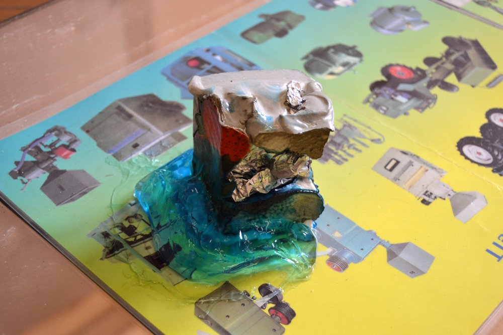 """Paperweight #1, detail, 2015/16, Installation view, materials: Concrete with cardboard, aluminium foil and expanded foam, blue """"Hair Code"""" gel, laminated company brochure (installation view), Roughly 6 x 6 x 6 cm. Photo: Nile Sunset Annex"""