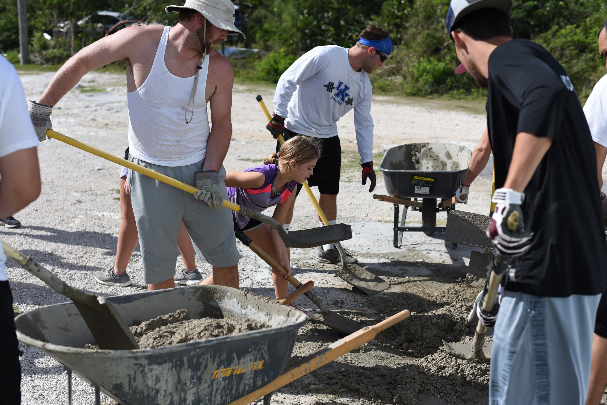 Mixing concrete to put in a basketball court for kids on the island