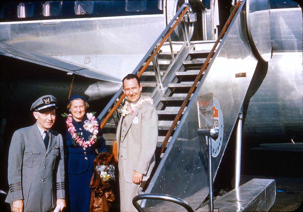Passengers pose with the captain as they disembark a United Stratocruiser at Honolulu.
