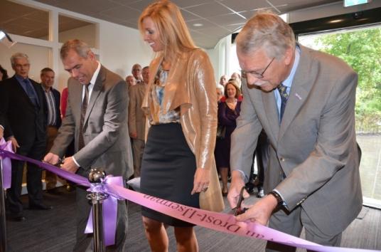 Directeur Wendy Hopmans kijkt toe hoe Jan Verbeek (links) en Ad van der Eijk de officiële opening verrichten.