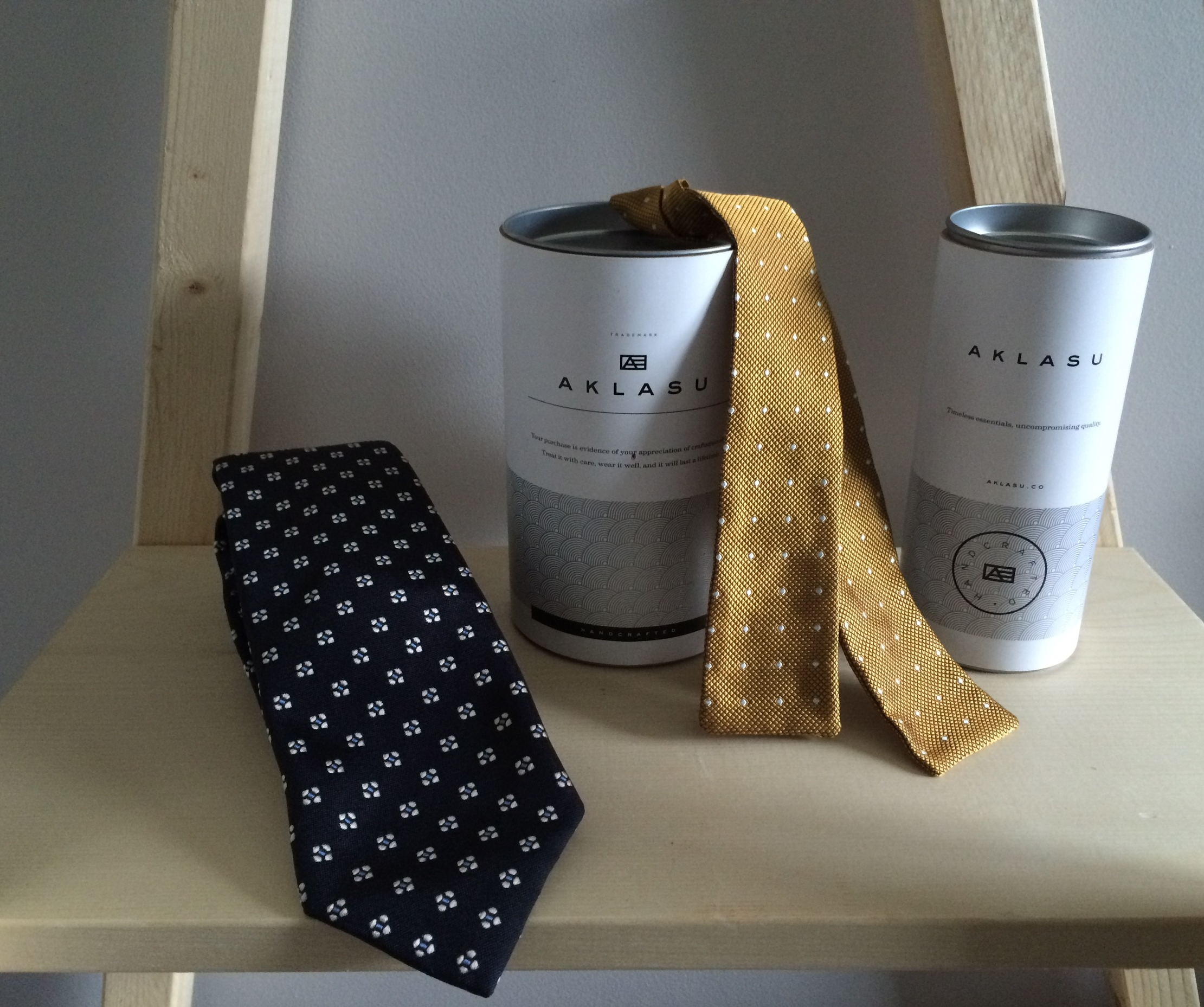 AKLASU tie, bowtie and storage canisters.
