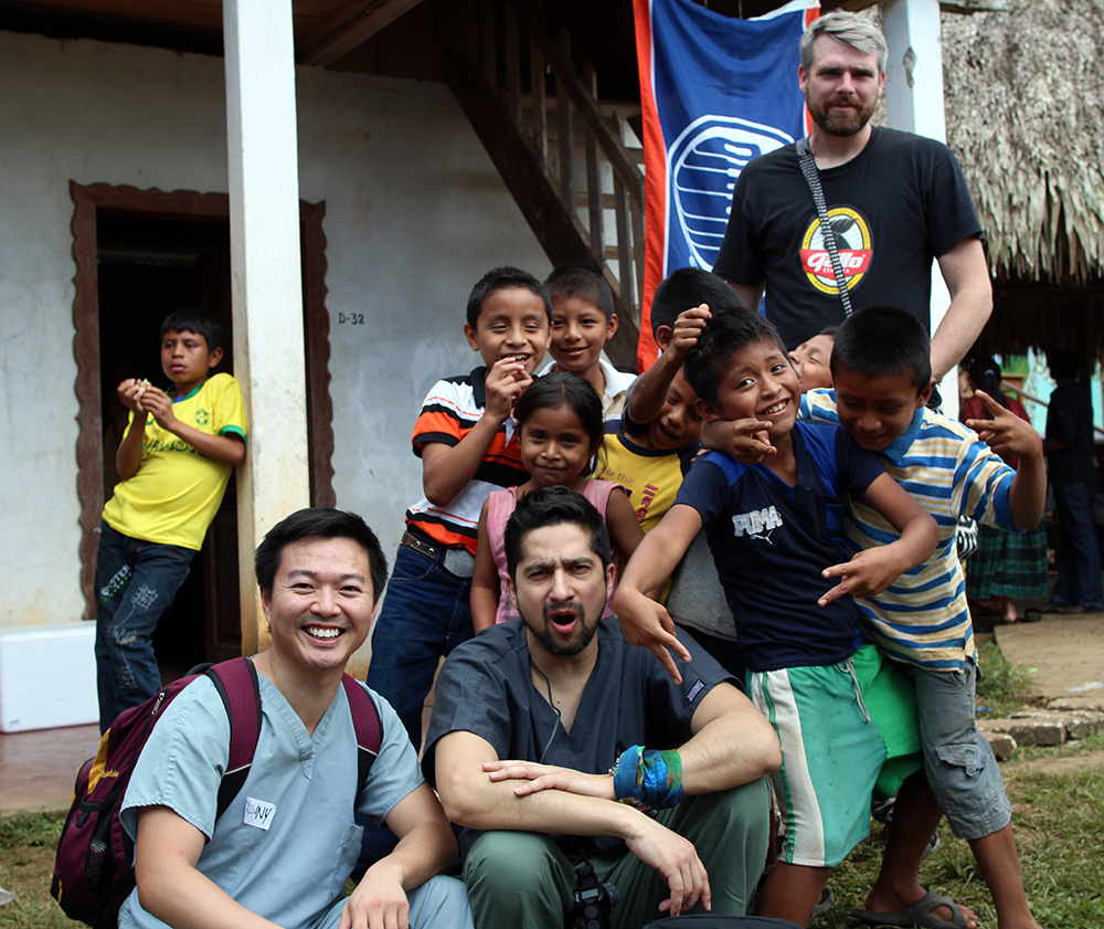 Dr. Leong and other mission team members get their picture taken with some local Chisec children. (You'll note the prominence of the Oilers flag on the facility.)