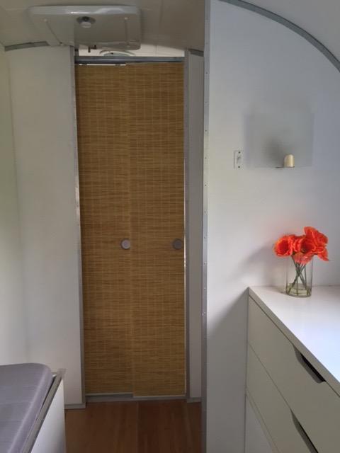 Sliding bathroom doors surfaced with grass cloth