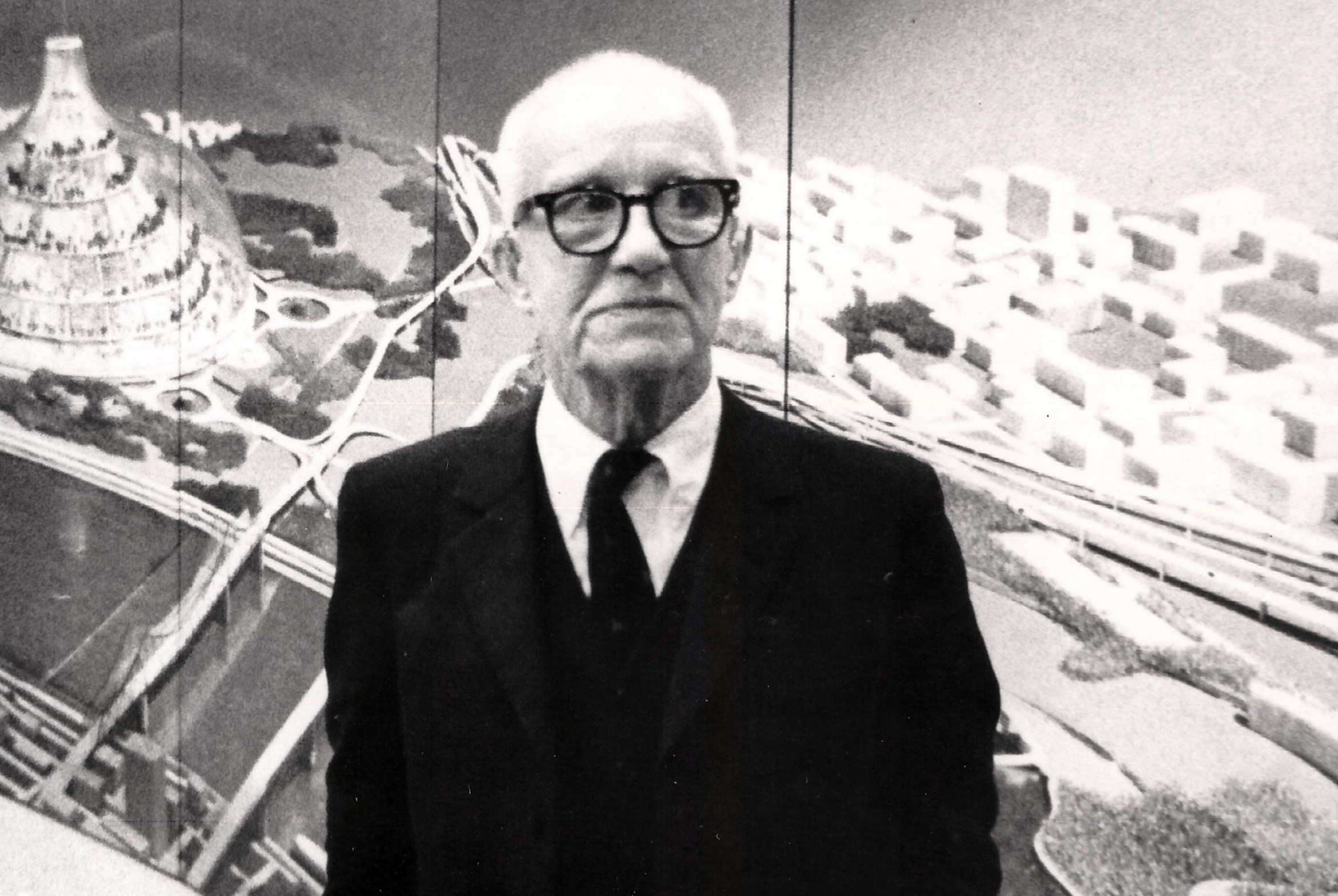 R. Buckminster Fuller stands in front of a depiction of his domed city design at its first public showing at a community meeting in East St. Louis, Illinois. Date  1971