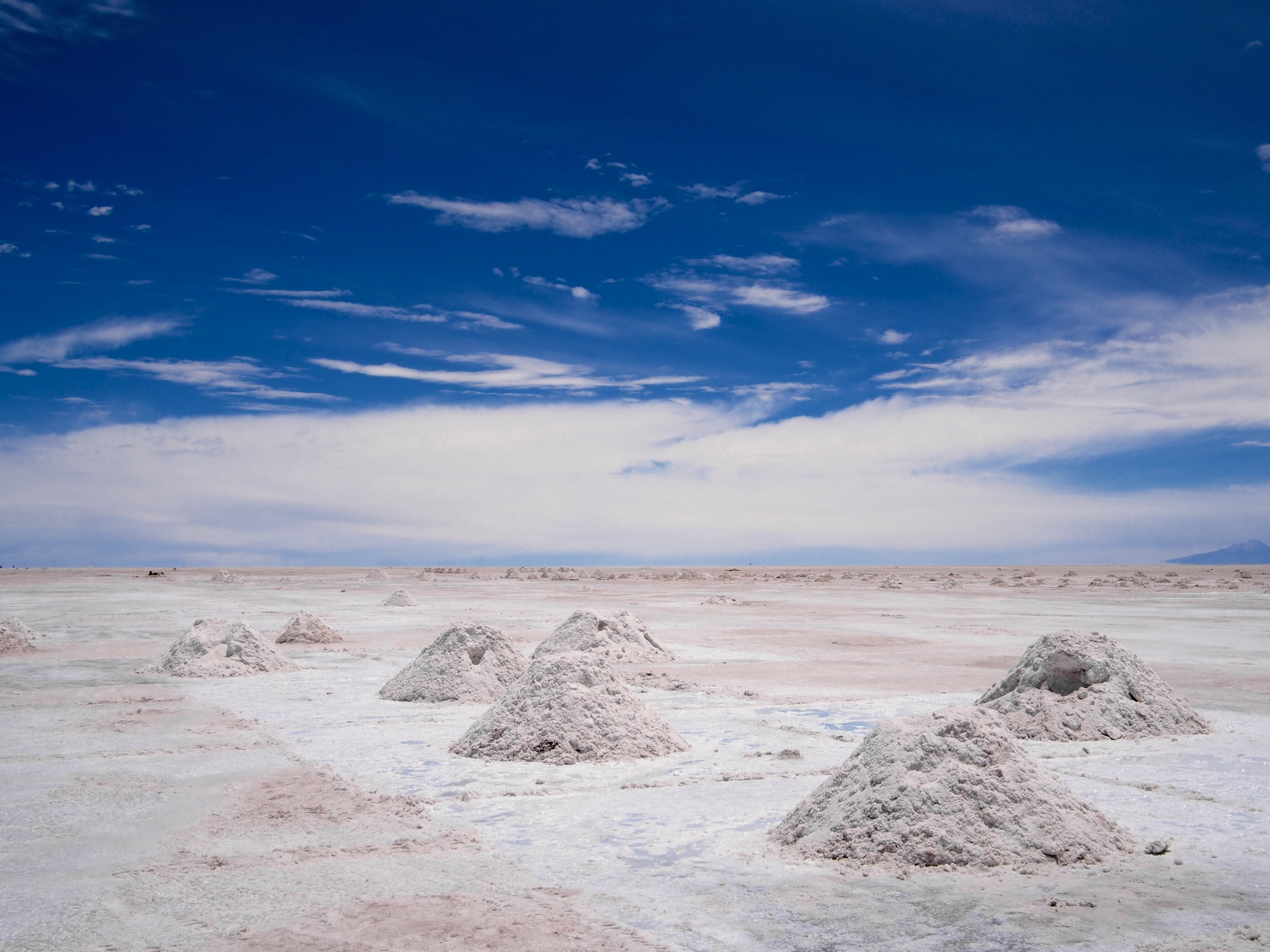 Salt is scraped off and piled into mounds ready to be transported and processed in Colchani, Bolivia