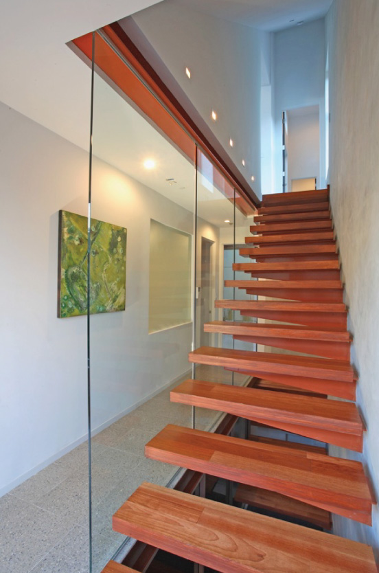 Floating rectangles are a theme carried throughout the house from the earth-toned panels on its facade and window framing, to the floating staircase made of steel and wood.