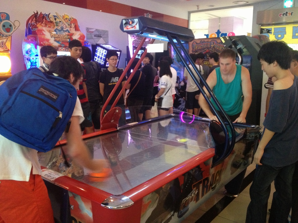Jamie and Craig playing air hockey, with a small crowd of local kids watching on