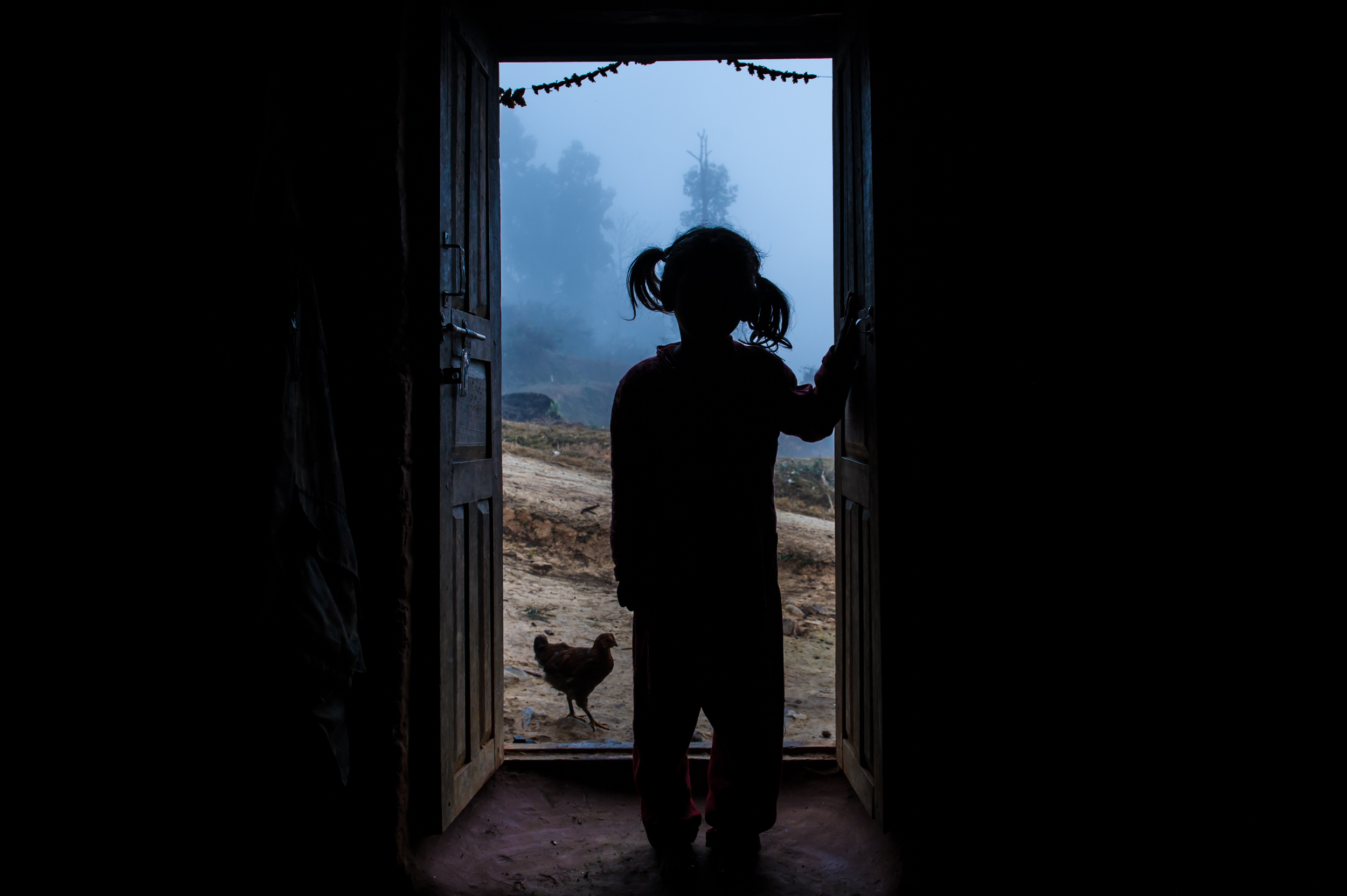 Rasu, who is in first grade at Shringery Secondary School, looks out the open front door. Despite the sun barely being up, her mother has already left to work on a construction site.