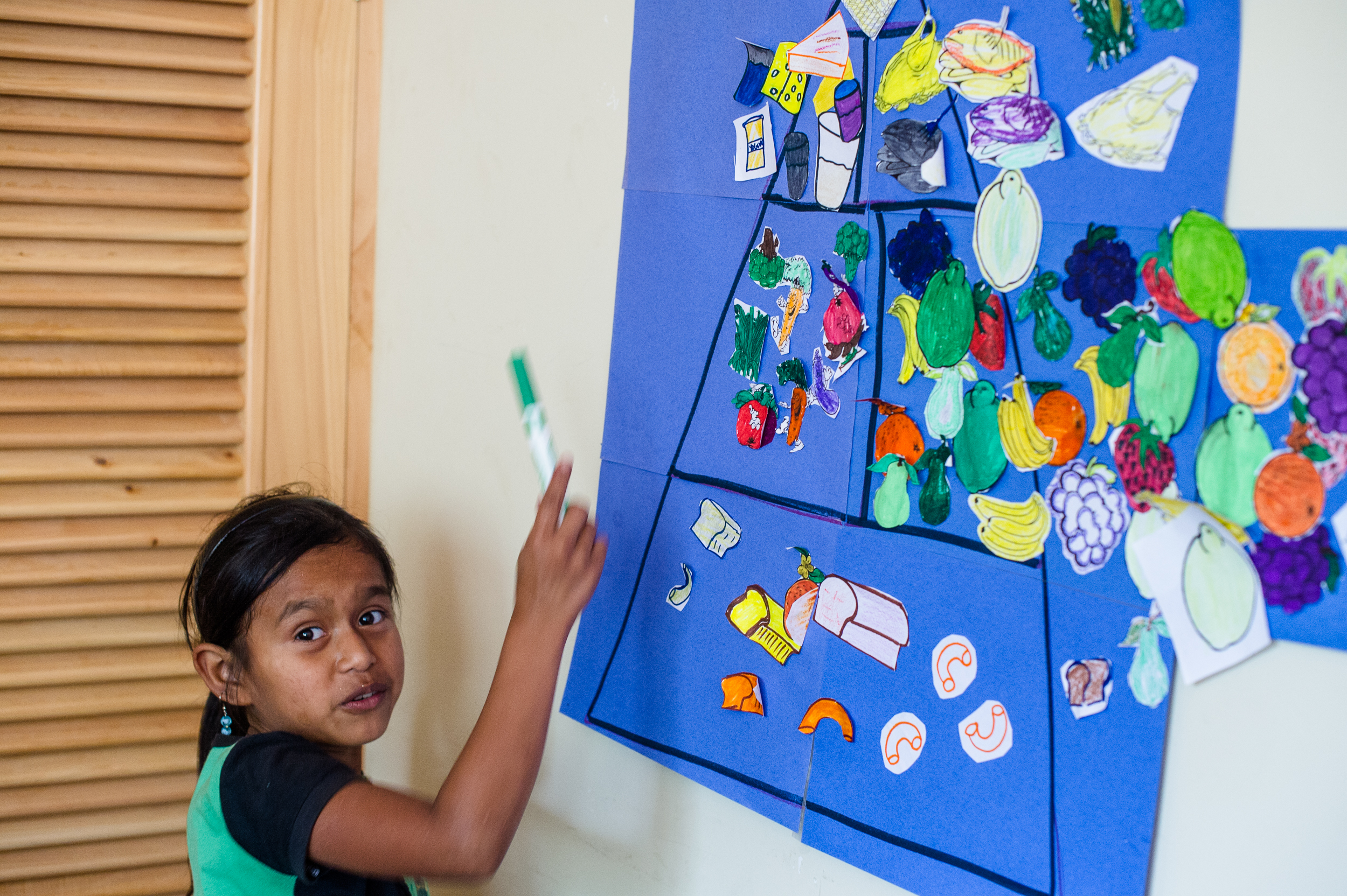Esperanza leads the class through an activity on the food pyramid. While Santa Cruz remains a difficult place to reach, junk food is pervasive. Some mothers put cola in their infant children's baby bottles because they confuse the spike in attentiveness that comes with a high dose of sugar and caffeine with it being nutritious.