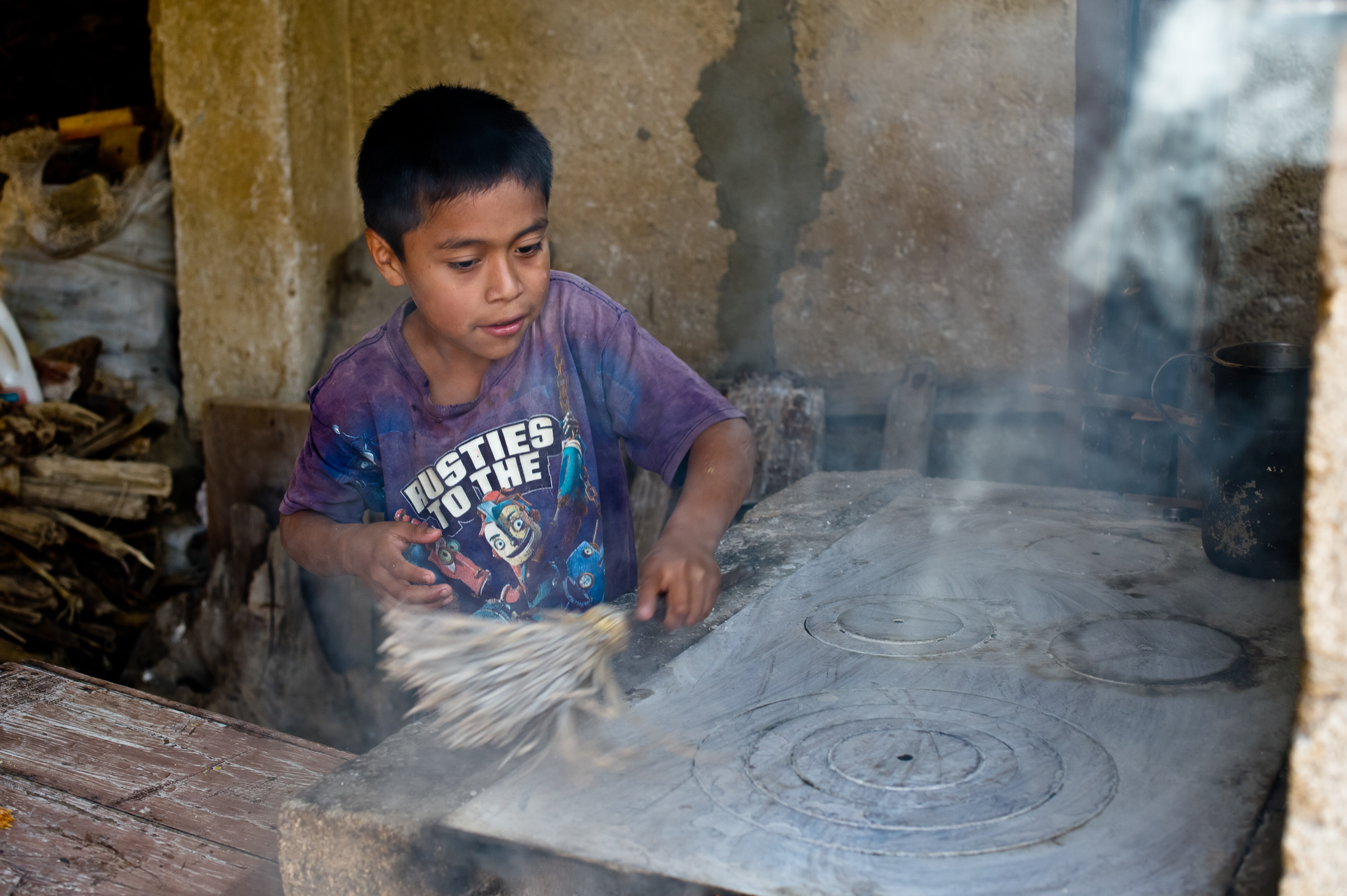 Maria's grandson cleans the family's grill. The family cooks in their open courtyard in front of their modest two-room home.