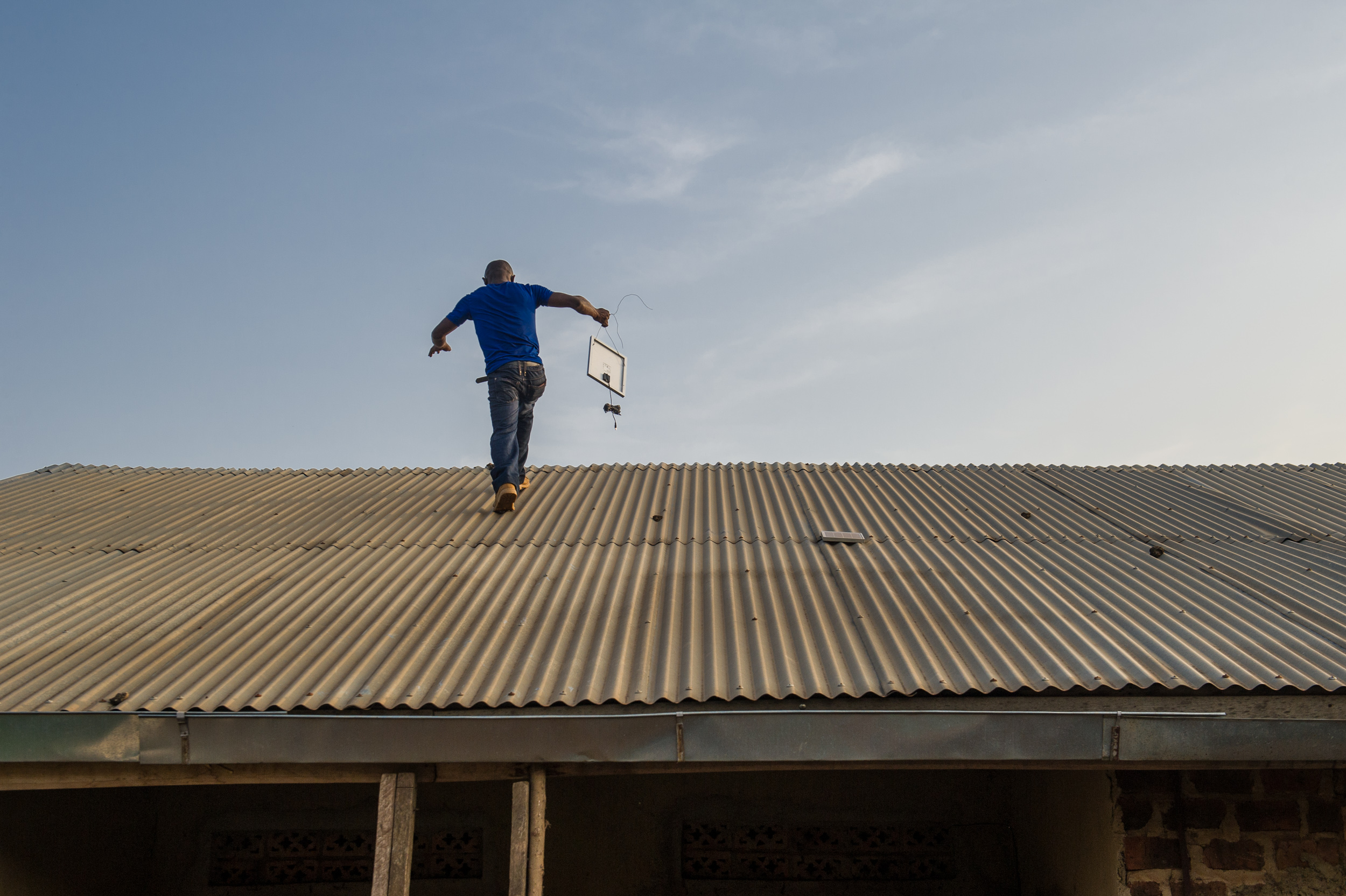 Abubaker, an electrician, installs a small solar panel on the roof.